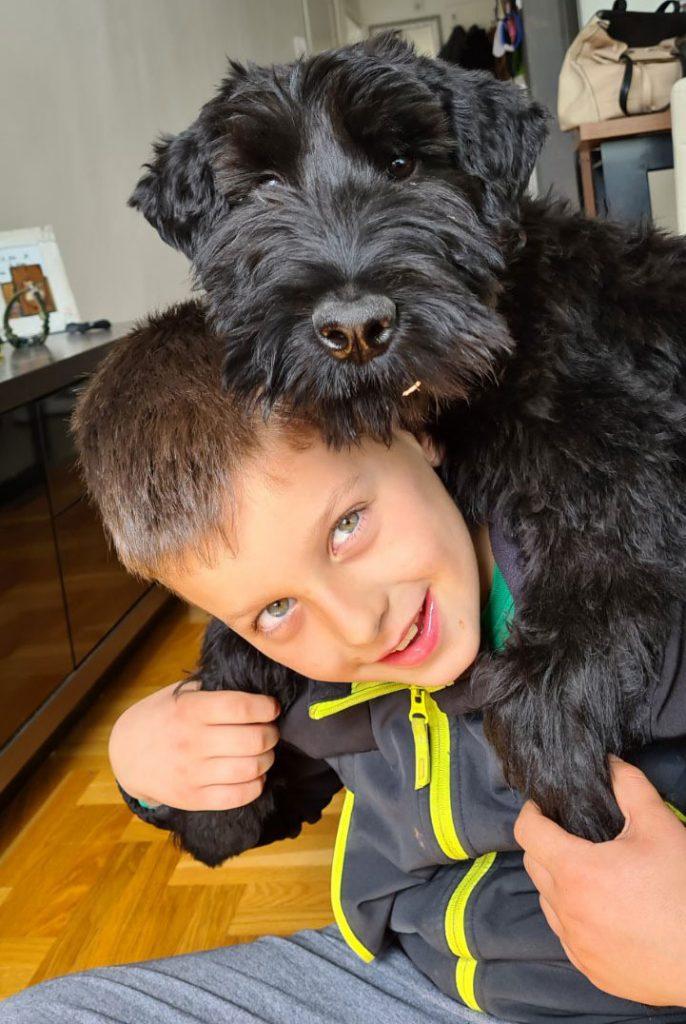 crni pas zagrlio dječaka